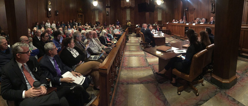 A packed committee room listens to testimony